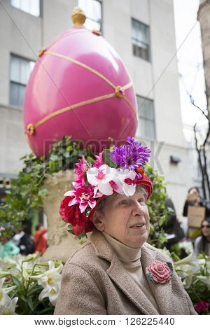 NEW YORK - MAR 27 2016: A woman sits by a giant Easter egg at Rockefeller Center Channel Gardens off 5th Ave Easter Sunday at the traditional Easter Bonnet Parade in Manhattan on March 27, 2016.