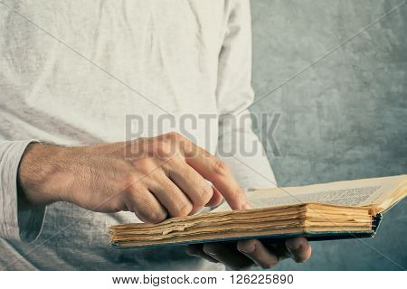 Man reading old book with torn pages close up of adult male hands holding vintage book.