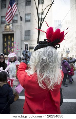NEW YORK - MAR 27 2016: A woman in red wearing a fancy Easter bonnet it takes pictures of parade goers on 5th Ave Easter Sunday at the traditional Easter Bonnet Parade in Manhattan on March 27, 2016.
