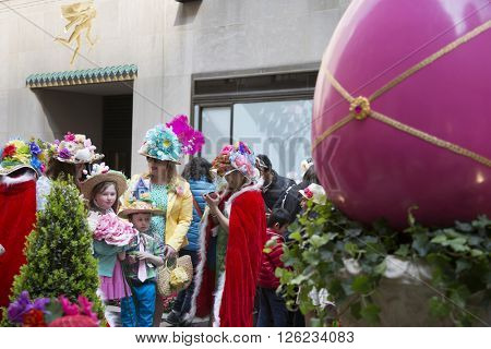NEW YORK - MAR 27 2016: A family gathers for photos by a giant Easter egg at Rockefeller Center Plaza off 5th Ave Easter Sunday at the traditional Easter Bonnet Parade in Manhattan on March 27, 2016.