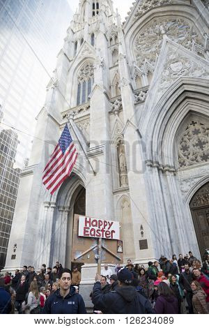 NEW YORK - MAR 27 2016: A man holding a religious sign with Happy Easter on the back in front of St Patricks Cathedral Easter Sunday at the Easter Bonnet Parade in Manhattan on March 27, 2016.