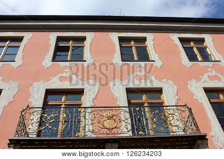Building facade windows ornamented with frescoes and balcony. Red building facade windows rows decorated with classic paintings. Hand crafted iron balcony with golden ornaments. Patterns of building decorations. Crafted details of old house.