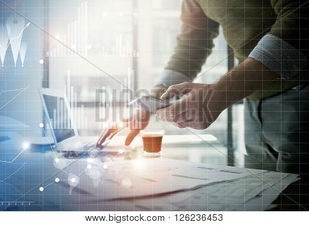 Business concept picture.Businessman working new startup project modern office.Holding contemporary smartphone hands. Worldwide connection technology, stock exchanges graphics interface.
