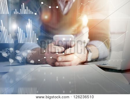 Business concept picture.Account manager working new startup project modern office.Holding contemporary smartphone hands. Worldwide connection technology, stock exchanges graphics interface.