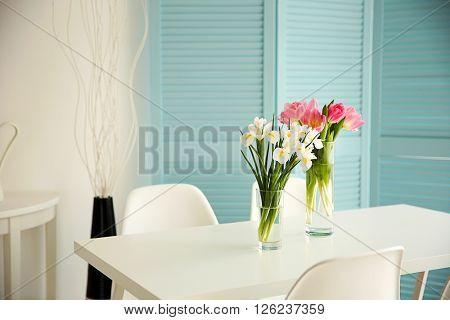 Beautiful tulips and irises on dinning table , indoors
