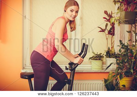Woman On Exercise Bike Listening Music. Fitness