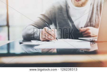 Investment manager work process.Photo man working paper documents. Private banker using pen for signs contracts. New business project startup. Flares and film effects