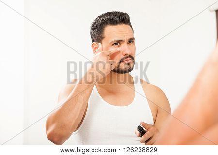 Hispanic Man Using An Under Eye Cream