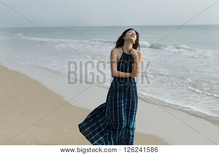 Lady in dark blue dress wandering on the beach