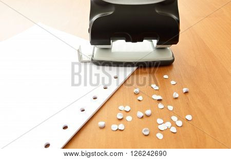 Hole puncher with paper and confetti on the office table