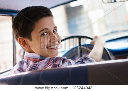 Preteen child learning to drive. He holds the volante of a vintage car from the 60s. He is amazed and excited. The boy smiles happy looking at camera.
