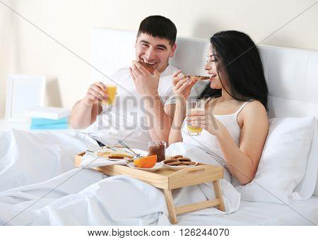 Lovely couple having breakfast in bed