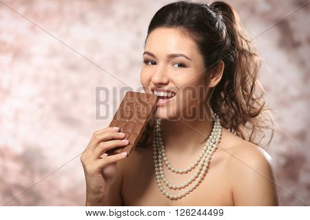 Portrait of beautiful young woman with chocolate on blurred background, close up