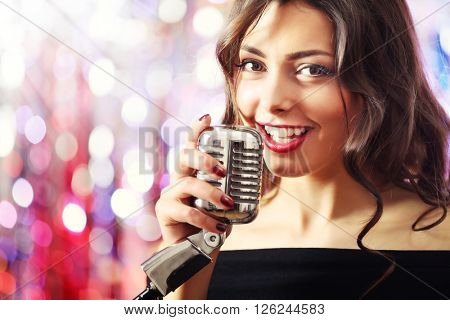 Portrait of beautiful singing woman against bright glitter background