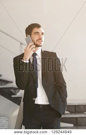 Man in suit talking on the mobile phone on the stairs
