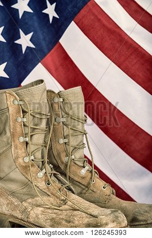 Old combat boots with American flag in the background. Vintage filter effects.