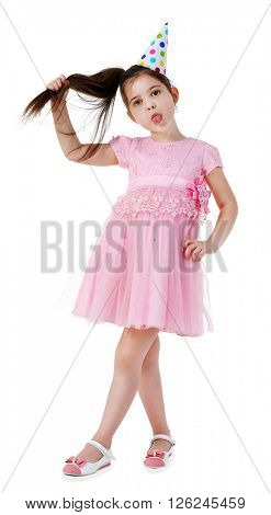 Little funny girl in birthday cap and pink dress, isolated on white