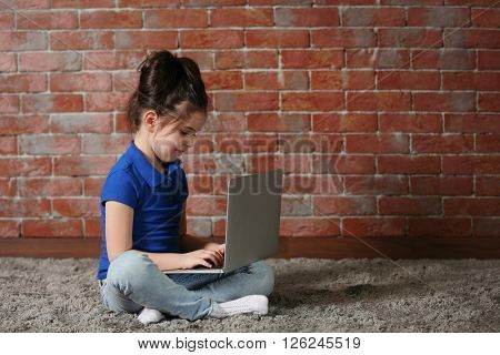 Little girl using laptop on fur carpet against brick wall background