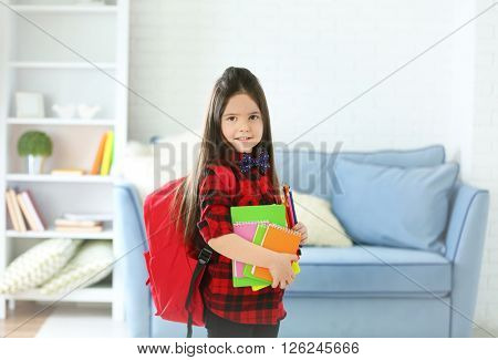 Little girl with red back pack holding notebooks and pencils in living room