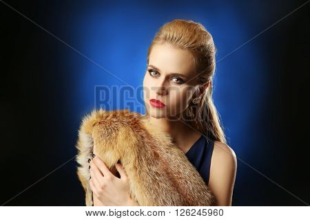 Young beautiful blonde girl wearing perfect makeup in a fox fur posing over dark-blue studio background