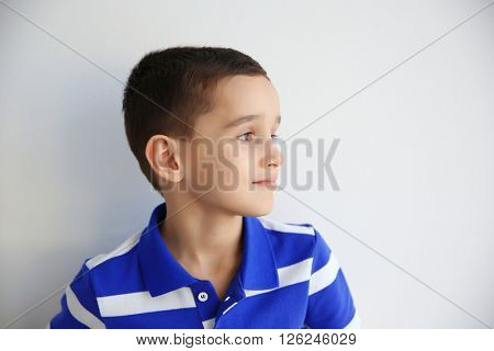 Portrait of little boy on white wall background