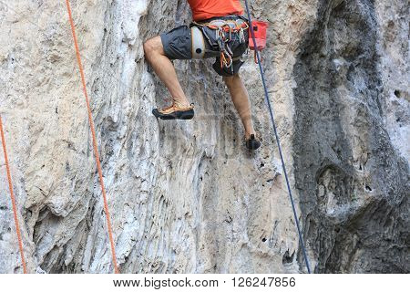 closeup of male rock climber legs climing