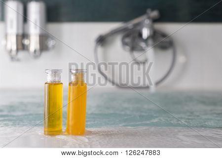 Background series : Bottle of shampoo and bath gel on the edge of bathtub