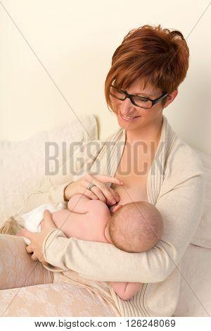 Tender mother breastfeeding her 7 week old baby in bed