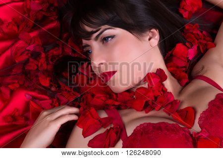 Young woman lying in a bed of red rose petals