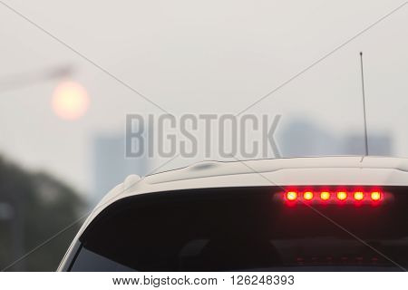 Third brake lights of white car in foggy evening