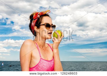 Attractive woman pinup in sunglasses eat green apple