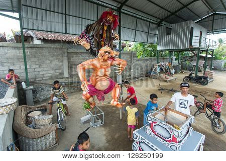 BALI, INDONESIA - MAR 7, 2016: Unidentified local people during built Ogoh-ogoh are statues for the Ngrupuk parade, which takes place on the eve of Nyepi day. Nyepi is a public holiday in Indonesia.