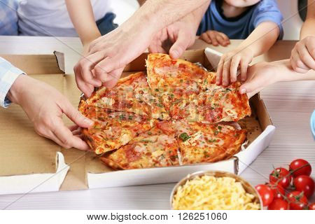 Happy family eating pizza on the wooden table