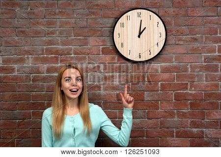 Young beautiful woman and clock on brick wall