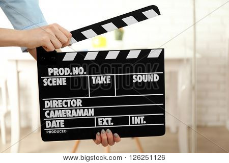 Woman hands holding film clapper, close up