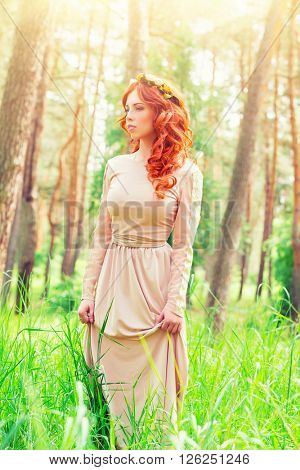 Dreamy girl standing in a forest on sunny spring day, wearing long elegant dress and flower wreath on curly red hair, fashion look