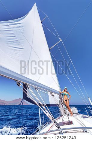 Sexy woman relaxing on sailboat, beautiful sexy model posing on luxury water transport, active summer holidays, enjoyment and pleasure concept