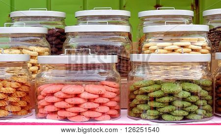A colorful selection of cookies sold from large glass jars.