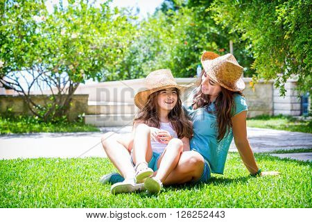 Happy family in the garden, beautiful mother with her little cute daughter sitting on fresh green grass on backyard, with pleasure spending time together