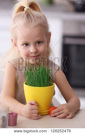 Little girl with plant at the wooden table closeup