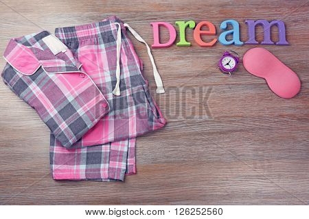 Word Dream with pajamas and sleeping mask on a wooden background