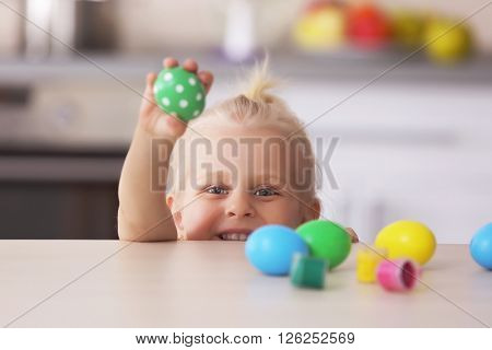 Little girl at the wooden table with painted Easter eggs in the kitchen
