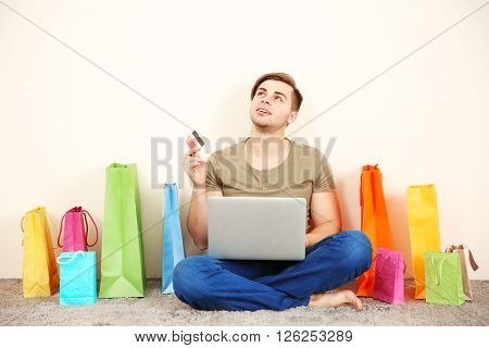 Young man doing online shopping with laptop and credit card indoors