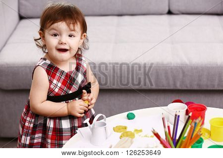 Little girl with paints in the room