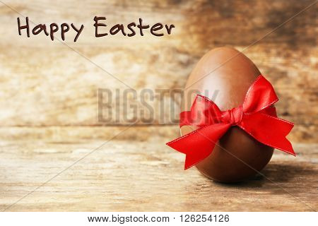 Chocolate Easter egg on wooden background.Retro stylization