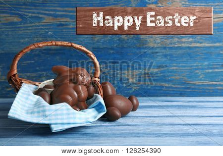 Easter chocolate bunny and eggs on wooden background. Retro stylization