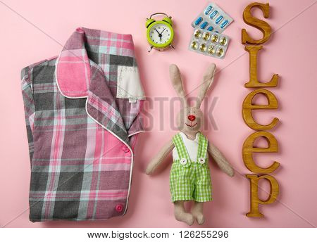 Insomnia concept. Sleeping accessories on pink background