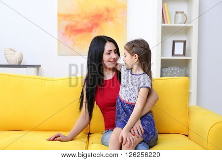 Mother and daughter sitting on the yellow sofa.