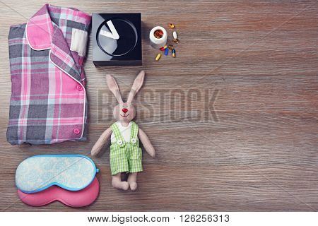 Little toy, pajamas and masks on a wooden background