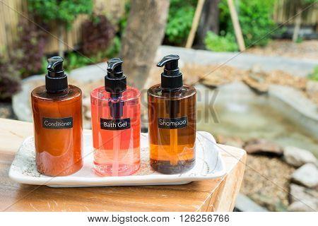 Bathroom amenity set in wooden tray, shampoo, bath gel and conditioner
